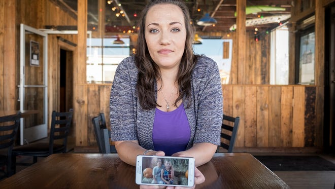 Desiree Redmond shows a photo of two of her sons. Redmond was addicted to opioids when she gave birth to her youngest son, who was born dependent to methadone and had to be weaned off of the drug over a five-day period.