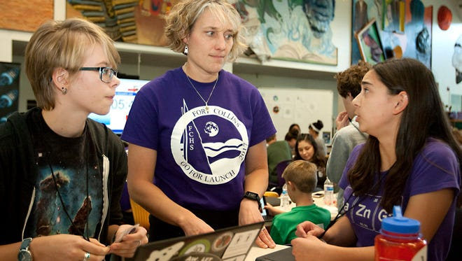 Astronaut Dottie Metcalf-Lindenburger, middle, listens as Skylar Beneck, right, discusses her space experiment idea as her partner Rachel Weiss looks on during Higher Orbits' Go For Launch! program held at Fort Collins High School Saturday afternoon. There were more than 50 kids in grades 8-12 that participated in the three-day event.