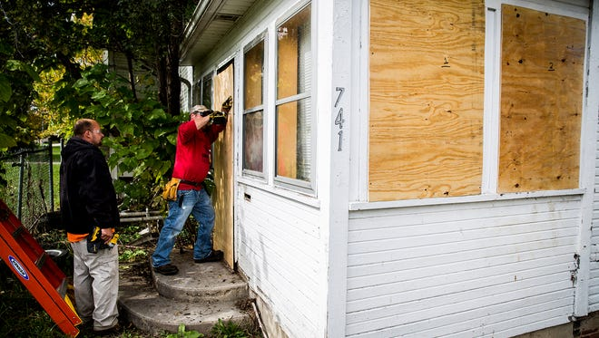 "City code enforcement workers Charles Chalfant and Robert Cox board the windows and doors of a property at 741 N. Mulberry St. in the McKinley Neighborhood near Central Wednesday afternoon. City workers and police officers performed a ""cleanup"" of the neighborhood Wednesday morning."