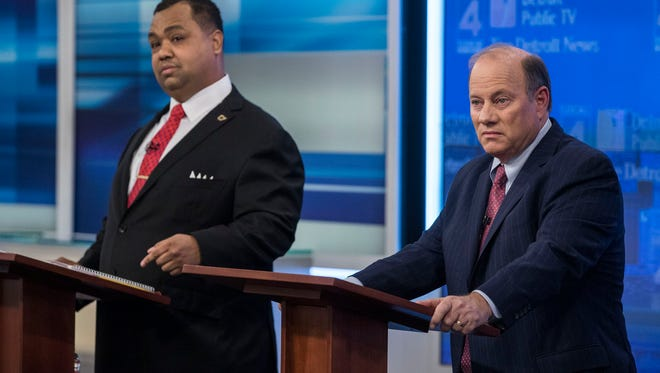 Mayoral candidates Coleman Young II, left, and Mike Duggan get ready for their debate last month.
