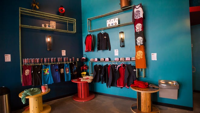 Lyric Cinema branded clothing and pint glasses sit on shelves on Thursday, Nov. 2, 2017 at Lyric Cinema Café's new location on North College Avenue in Fort Collins, Colo.
