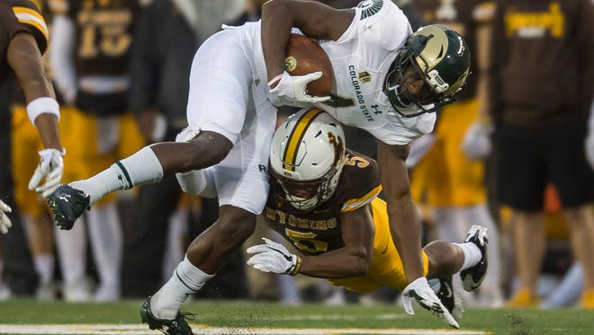 CSU receiver Michael Gallup is tackled by Wyoming defender Rico Gafford during Saturday night's game in Laramie, Wyo. The Cowboys beat the Rams 16-13.