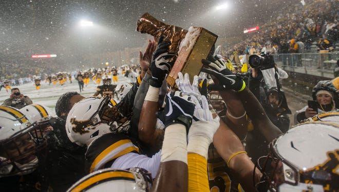 Wyoming players hoist up the boot after defeating CSU on Saturday, Nov. 4, 2017, at War Memorial Stadium in Laramie, Wyo.