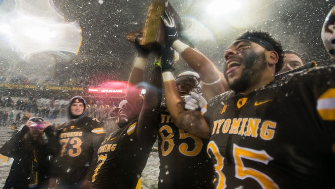 Wyoming players Chavez Pownell Jr. (7) Tyree Mayfield (85) and Jaylon Watson (35) hoist up the boot after defeating CSU on Saturday, Nov. 4, 2017, at War Memorial Stadium in Laramie, Wyo.