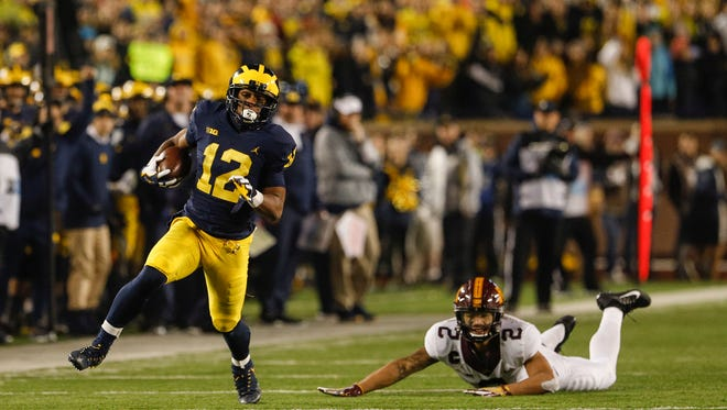 Michigan running back Chris Evans (12) runs with the ball and chased by Minnesota defensive back Jacob Huff (2) during the first half at the Michigan Stadium in Ann Arbor, Saturday, November 4, 2017.