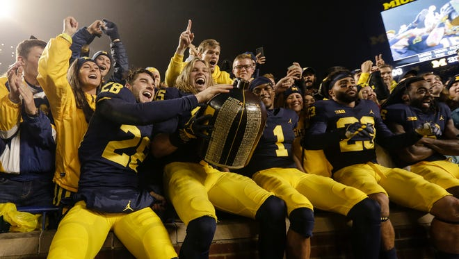 Michigan players include defensive back Brandon Watson (28), defensive line Chase Winovich (15), defensive back Ambry Thomas (1) celebrate their 33-10 victory over Minnesota with the Little Brown Jug at student section at the Michigan Stadium in Ann Arbor, Saturday, November 4, 2017.