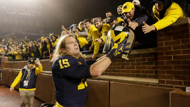 Michigan defensive line Chase Winovich (15) runs around the the Michigan Stadium with the Little Brown Jug to celebrate the Wolverines' 33-10 victory over Minnesota in Ann Arbor, Saturday, November 4, 2017.
