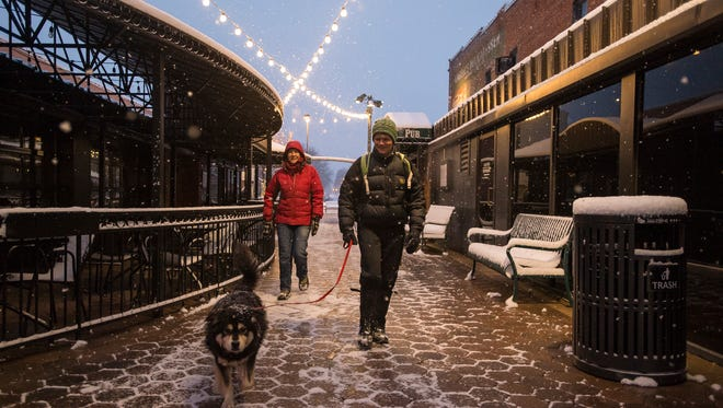 Laura Larson, left, and Jessica Rykken take Tuuli for a walk through Old Town Square on Tuesday, the day of Fort Collins' biggest snowfall of the year so far.