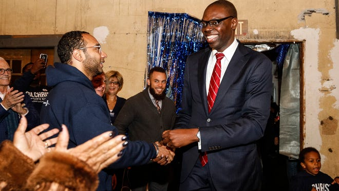 City clerk candidate Garlin Gilchrist, center, shakes hands with election volunteer Brandon Celestin of Detroit as he walks into Jam Handy in Detroit, Tuesday, November 7, 2017.