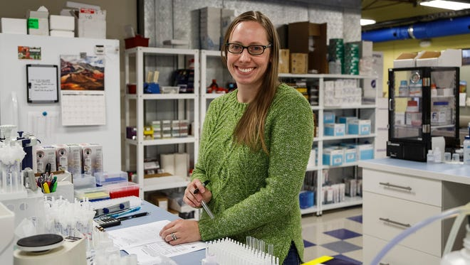 Elizabeth Raymond, quality control scientist, poses for a photo in the lab at the Arbor Assays office in Ann Arbor, Thursday, November 9, 2017.
