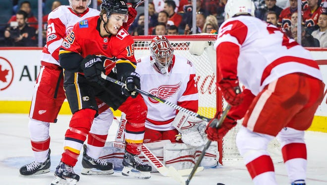 Flames left wing Matthew Tkachuk (19) and Red Wings defenseman Xavier Ouellet (61) battle for the puck in front of Wings goalie Petr Mrazek on Thursday in Calgary.