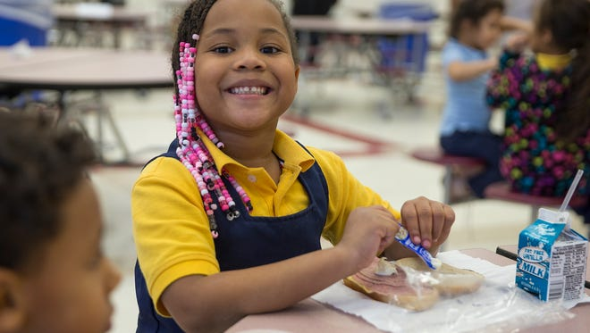 Jhala grins for the camera while eating an after-school meal at Global Prep Academy at Riverside 44. The Boys & Girls Club program includes homework help, exercise and a meal. A grant from IndyStar's Our Children initiative contributes to its funding.