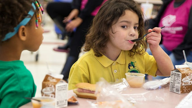 At right, Lilly takes a bite of applesauce at the start of a Boys & Girls Club after-school program at Global Prep Academy at Riverside 44, Indianapolis, Friday, Nov. 10, 2017. A $4,500 grant from IndyStar's Our Children initiative contributes partially to the program's funding. In 2017, Our Children has granted out $175,000 in Indianapolis to help fight childhood hunger.