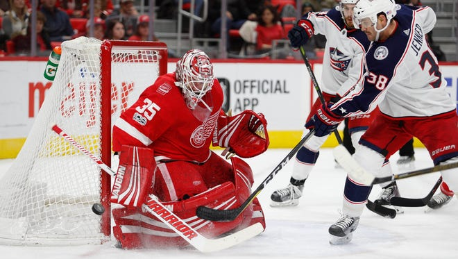 Red Wings goalie Jimmy Howard (35) makes a save against Blue Jackets center Boone Jenner (38) during the first period ,