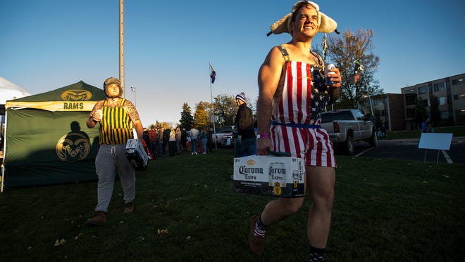 John Miller, right, and Tyler Mace walk through a tailgate area before a Homecoming game against Nevada on Saturday afternoon, Oct. 14, 2017, on campus in Fort Collins, Colo.