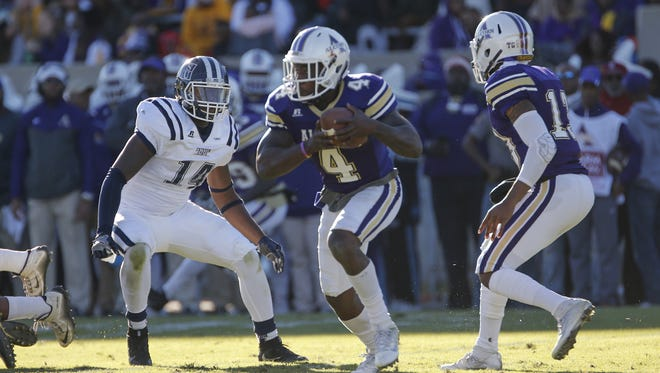 Alcorn State tailback Silas Spearman takes the handoff from quarterback Noah Johnson and runs past JSU defender Keontre Anderson during the 2016 edition of the Jackson State-Alcorn State rivalry.