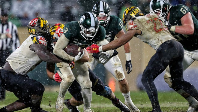 Michigan State Spartans running back LJ Scott (3) breaks the tackle of Maryland Terrapins linebacker Isaiah Davis (22) during the second half of the game against Maryland on Saturday, Nov. 18, 2017, at Spartan Stadium.