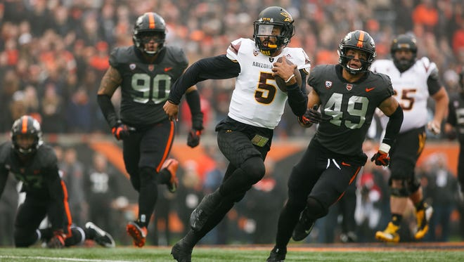 Arizona State player Manny Wilkins carries the ball past Oregon State defenders at Reser Stadium.