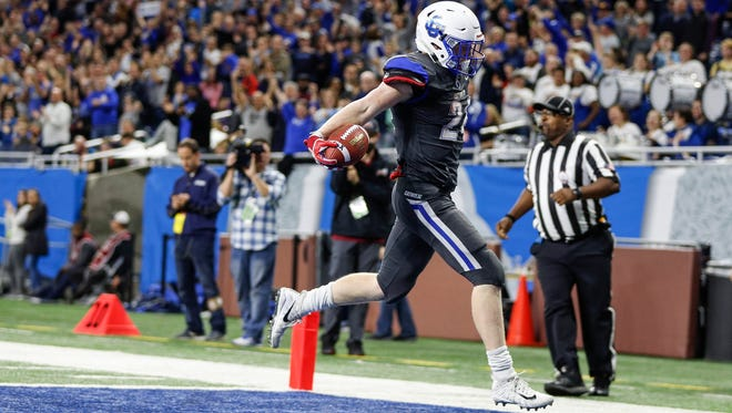 Grand Rapids Catholic Central's Nolan Fugate (24) celebrates as he runs into the end zone for a touchdown during the second half of Catholic Central's 42-31 win over Edwardsburg in the Division 4 state title game on Friday, Nov. 24, 2017, at Ford Field.