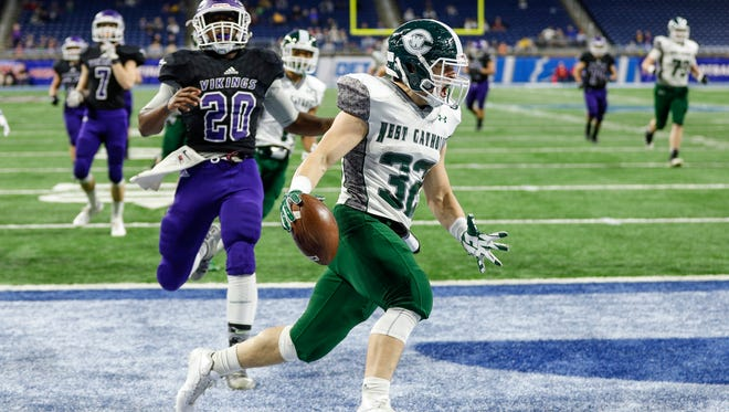 Grand Rapids West Catholic running back Zack Lee (32) celebrates after scoring a touchdown during the first half of the Division 5 state title game on Saturday, Nov. 25, 2017, at Ford Field.