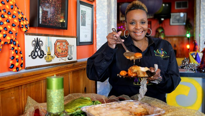 Alcenia's owner B.J. Chester-Tamayo shows off a piece of her sweet potato cobbler in her restaurant, located at 317 N. Main St.