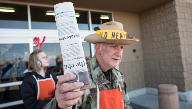 Old Newsboys volunteer Ed Burtch Jr. holds out a copy of the Times Herald outside of Sam's Club in Port Huron Dec. 1. Burtch has been volunteering for 61 years.