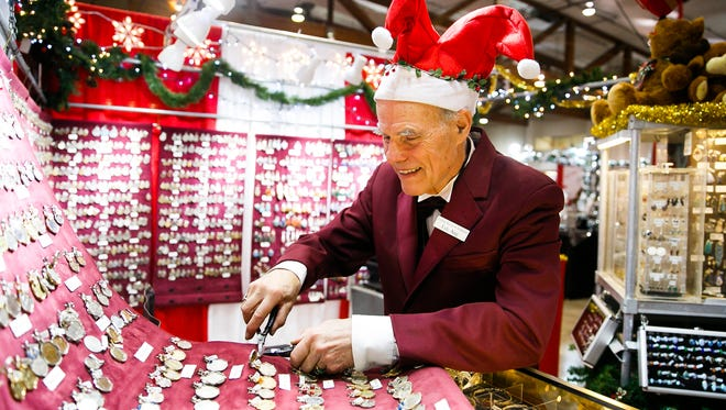 Lyle Ang of Mill City, Ore., adjusts some of his pendants made from foreign coins at the 18th annual Salem Holiday Market on Saturday, Dec. 9, 2017, at the Oregon State Fairgrounds. And and his wife Vivian showcased their jewels and pendants at their Living Stones Creations booth for their twelfth time at the holiday market.