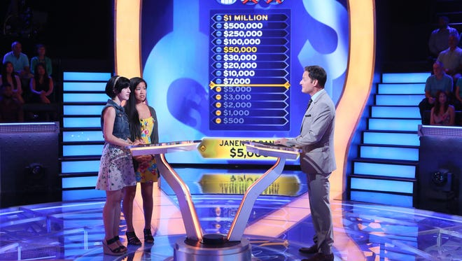 Janene Marcus, left, and her friend Emily Huang with host Chris Harrison on the set of Who Wants to Be a Millionaire