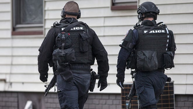 Members of SWAT, Indianapolis Metropolitan Police Department and other safety responders patrol the area after an officer was shot while serving a narcotics warrant in the 2100 block of Spann Avenue, Indianapolis, Wednesday, Dec. 13, 2017. The officer was shot at and returned fire at the suspect.