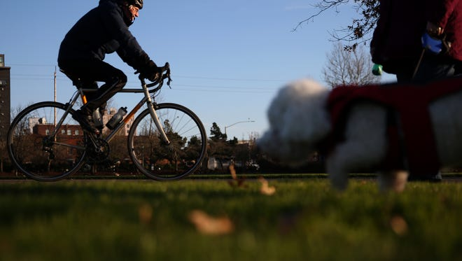 A bicyclist rides past a woman walking her dog in the sun at Riverfront Park in Salem on Monday, Dec. 11, 2017.