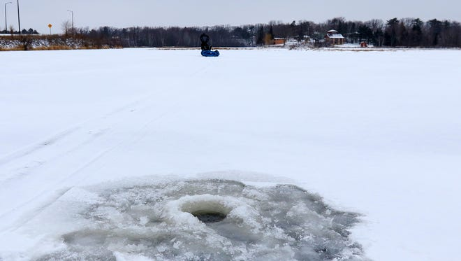 An ice fishing hole drilled Wednesday, Dec. 13, 2017, on Wisconsin River near McCleary Bridge in Wausau, Wis.