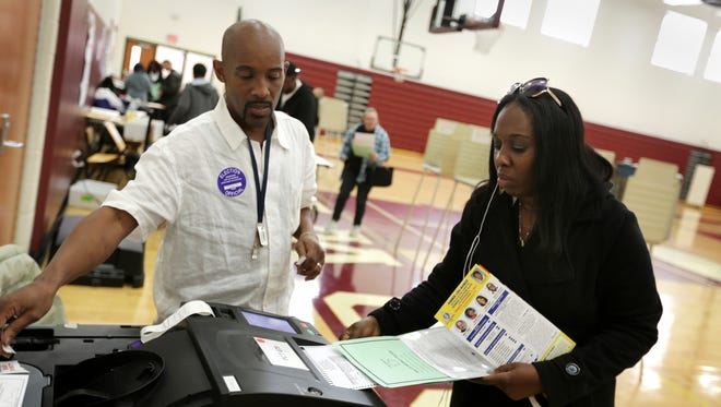 Christine Byrdsong, 48, of Detroit casts her vote under the supervision of ballot box inspector Michael Waters at Western International High School in Detroit in November 2017.