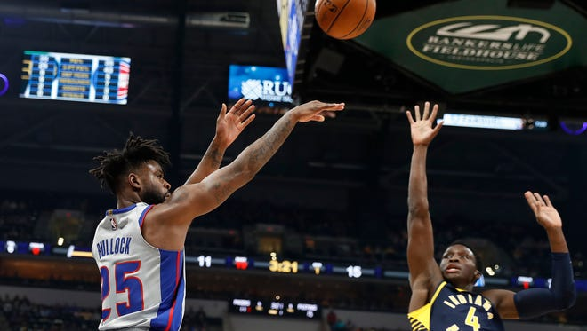 Pistons forward Reggie Bullock (25) takes a shot against Pacers guard Victor Oladipo (4) during the first quarter on Friday, Dec. 15, 2017, in Indianapolis.