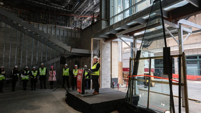 Ilitch Holdings Inc. President and CEO Christopher Ilitch talks with media after showing a window that will be part of the world's first pizza-slice-shaped window façade at the Little Caesars headquarters in downtown Detroit.