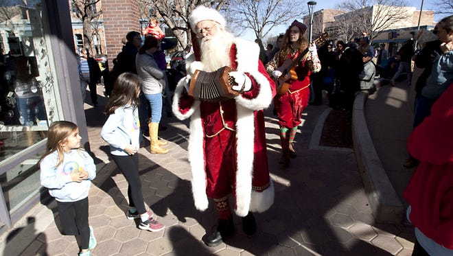 Santa and his elves play Christmas carols to a crowd in Old Town Square on their way to Santa's Holiday Workshop Saturday, Nov. 13, 2017.