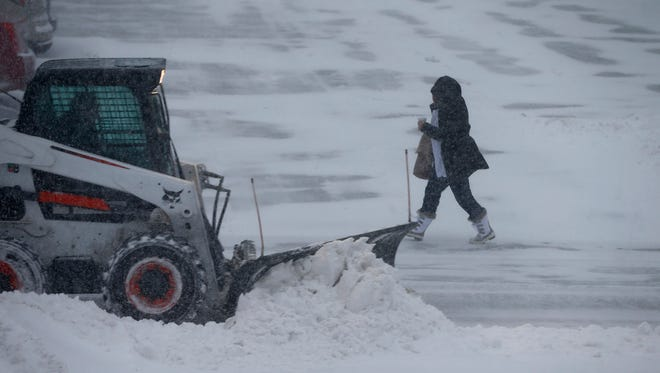 A woman walks past a snow plow at Ocean Medical Center in Brick Townhip Thursday morning, January 4, 2017.