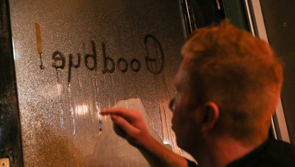"Server Kyle Mock writes ""Goodbye!"" in the window..."