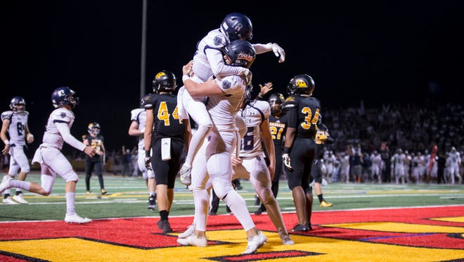 Defensive end Ty Robinson (87) and wide receiver Jacob Rowland (18) of the Higley Knights celebrate a touchdown in the 4A state playoffs against Saguaro Sabercats on Nov. 17, 2017.