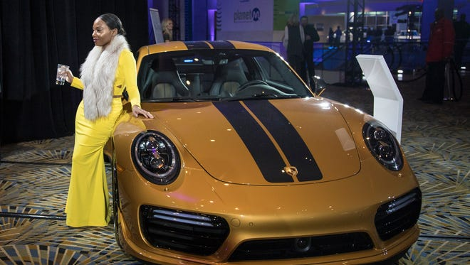 Akeila Richter poses for a photo for her husband Johann Richter (not in the photo), both of Los Angeles, Calif., in front of a 2018 Porsche 911 Turbo S Exclusive Series during the Gallery held at Cobo Center in downtown Detroit on Saturday, Jan. 13, 2018.