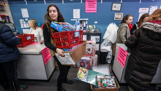 An employee takes toys from the front registers during the Liquidation sale at the Doll Hospital & Toy Soldier Shop in Berkley, Mich. on Thursday, Jan. 18, 2018. After 70 years the store is closing due to online purchasing competition.