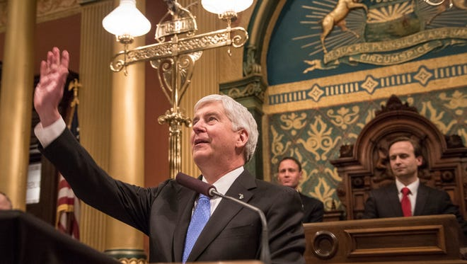 Michigan Gov. Rick Snyder waves at the crowd before his State of the State address in the House of Representatives Chamber at the State Capitol in Lansing on Tuesday, January 23, 2018.