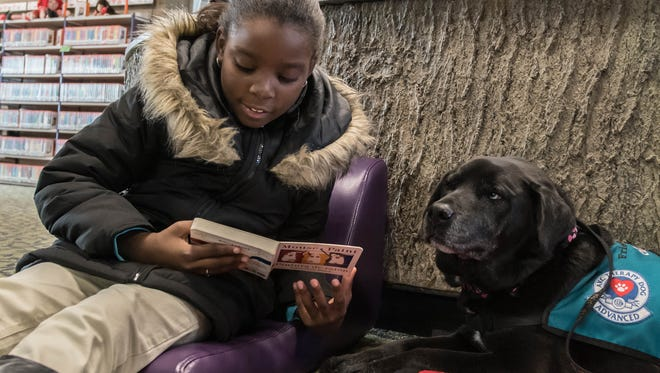 "Jha'Niece Turner reads to Sasha, a black lab mix as part of the  ""Paws to Read"" program at Willard Library on Thursday."