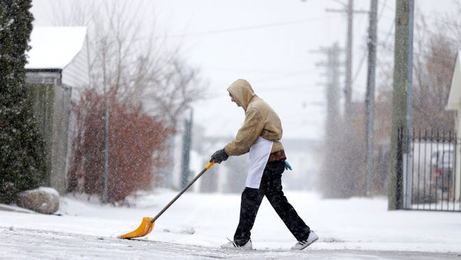 An employee at the Honey Bee Supermarket removes snow off the entrance to the store in southwest Detroit on Monday, Jan. 29, 2018.