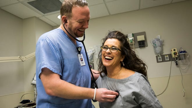 Carol Nemecek, right, tells a joke while Dr. Christopher Roskopp checks her heartbeat in the McLaren Port Huron emergency room Wednesday. In 2016, Nemecek suffered a massive heart attack, and Dr. Roskopp was the emergency room doctor who treated her.