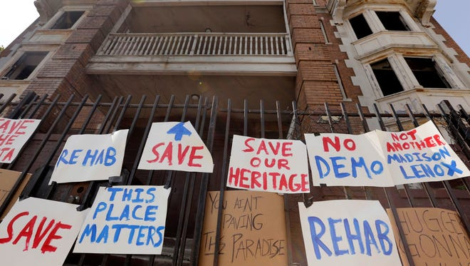 Signs hang on the fence around the Atlanta building on Cass Avenue where people gathered to raise awareness about the value of preserving historic buildings and asked that a group of buildings including the Atlanta and Hotel Ansonia not be demolished in Detroit on Thursday, August 24, 2017.