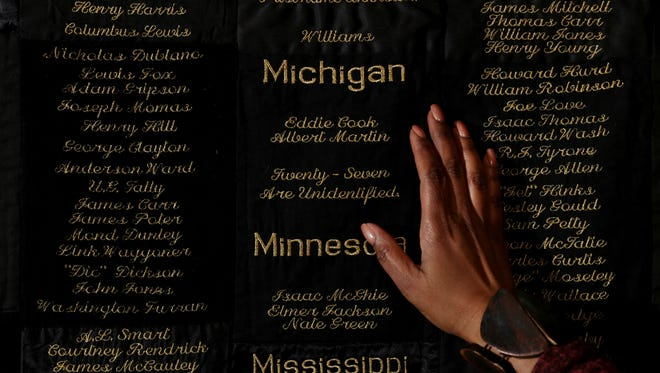 Fiber artist April Shipp places her hand on her quilt listing names of African Americans who were lynched and murdered between 1865 and 1965 at Detroit Unity Temple in Detroit, Wednesday, February 7, 2018.