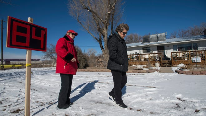 Longtime residents Loretta Keeton, right, and Yvonne Wittreich stand next to a sign marking 84 feet from the road that shows the extent that the proposed pipeline, that would carry millions of gallons of Poudre River water from reservoirs north of Fort Collins to the growing city of Thornton, might cut into Keeton's property on Tuesday, Feb. 13, 2018, on the 1000 block of East Douglas Road in Fort Collins, Colo. Both residents have marked how far into their property 84 feet would cut to serve as a visual reminder to others how much of their property could be taken and how close the new road would run next to their homes.