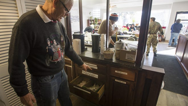 House of Neighborly Service volunteer Cal Gabelman shows some of the cabinets containing hygiene item for clients to use on Wednesday, Feb. 14, 2018, at 137 Connection in Loveland.