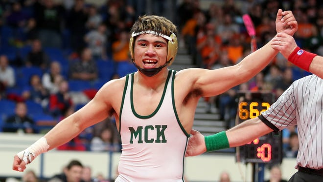 David Rubio has his hand raised after winning the 6A state championship at 170 pounds on Feb. 17, 2018, to become the second wrestler in school history to win a state title.
