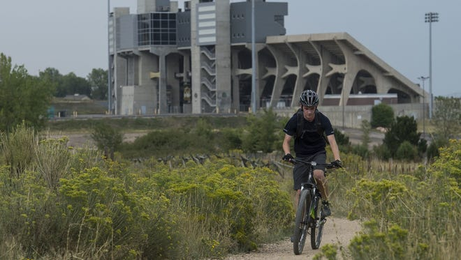 A cyclist makes his way south on the Foothills Trail past Hughes Stadium in August 2017 at Maxwell Natural Area.